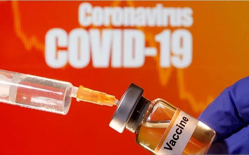 Sebuah botol kecil berlabel Vaksin diletakkan di dekat jarum suntik medis di depan tulisan Coronavirus Covid-19
