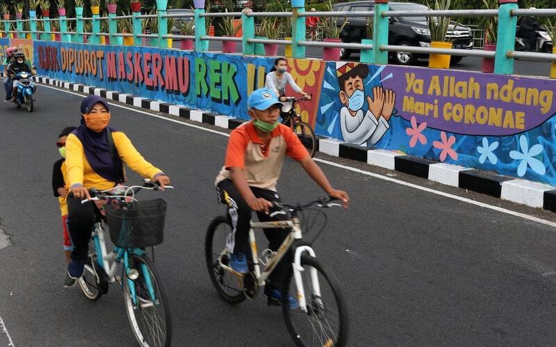 Sejumlah pesepeda melintas di dekat dinding bermural di Surabaya, Jawa Timur, Minggu (18/10/2020). Mural di sepanjang dinding viaduk Gubeng itu sebagai sarana imbauan kepada masyarakat untuk menerapkan protokol kesehatan pencegahan penularan Covid-19. - Antara/Didik Suhartono