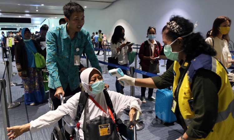 Petugas memeriksa suhu tubuh penumpang yang baru tiba di Terminal 3 Kedatangan Internasional Bandara Soekarno Hatta, Tangerang, Banten, Senin (2/3/2020).Bisnis - Eusebio Chrysnamurti