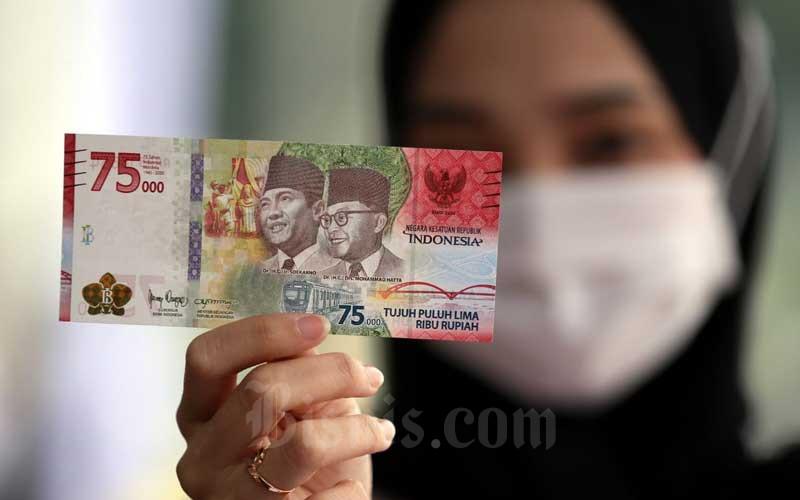 Warga memperlihatkan uang lembar pecahan Rp75.000 usai melakukan penukaran di Kantor Perwakilan wilayah Bank Indonesia (KPw BI) Jawa Barat, Bandung, Jawa Barat, Selasa (18/8/2020). Bisnis - Rachman