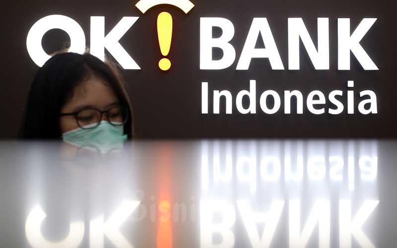 Karyawan berada di depan logo PT Bank Oke Indonesia Tbk. (DNAR) di Jakarta, Jumat (8/5/2020). Bisnis - Abdullah Azzam