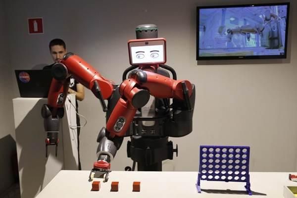 Robot Baxter memilih sebuah kubus, berisi lembaran dengan nama tim, ketika mencoba memprediksi hasil pertandingan semifinal Piala Dunia antara Prancis dan Belgia selama acara di paviliun Pameran Prestasi Ekonomi Nasional (VDNKh) di Moskow, Rusia, Selasa (10/7/2018) - REUTERS / Gleb Garanich