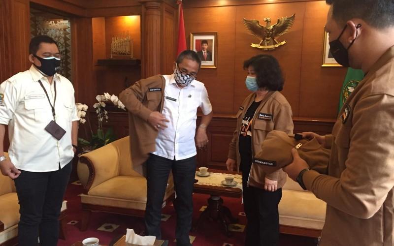 Kepala Biro Perekonomian Pemerintah Provinsi Jawa Barat Benny Bachtiar (kedua kiri) menerima jaket tim Jelajah Segitiga Rebana III dari Presdir JAG Lulu Terianto (kedua kanan) - Bisnis/Wisnu Wage