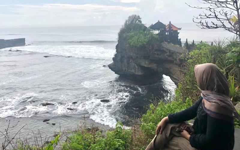 Seorang wisatawan menikmati keindahan Tanah Lot di Tabanan, Bali./Bisnis.com - M. Syahran W. Lubis