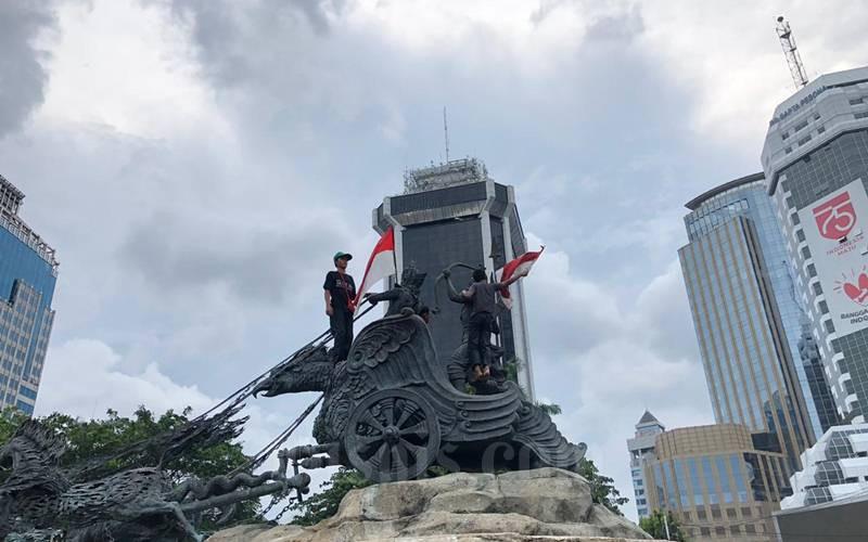 Dua remaja memanjat Patung Kuda Arjuna Wiwaha di Jalan Medan Merdeka Barat, Selasa (20/10/2020). Tindakan mereka memasang bendera Merah Putih menarik perhatian para demonstran yang berunjuk rasa menentang UU Cipta Kerja, Selasa (20/10/2020). - Bisnis/Aprianus Doni