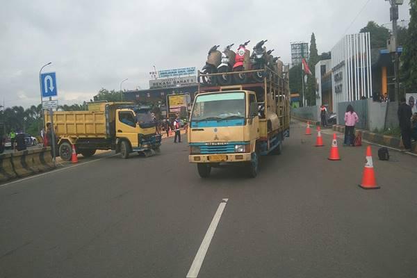 Truk melakukan putar balik di gerbang tol Bekasi Barat 1 saat pemberlakuan pembatasan kendaraan di jalan tol Jakarta-Cikampek, Senin (13/3/2018) - JIBI/Jaffry Prabu Prakoso