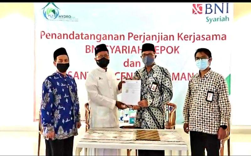 Pemimpin BNI Syariah Kantor Cabang Depok, Syarief Hidayat (dua dari kanan) melakukan penandatangan perjanjian kerja sama terkait pemanfaatan produk dan layanan perbankan syariah dengan Pimpinan Pondok Pesantren Cendekia Amanah, Depok Muhammad Cholil Nafis (dua dari kiri), Kamis (22/10/2020).  - Dok. BNI Syariah\r\n