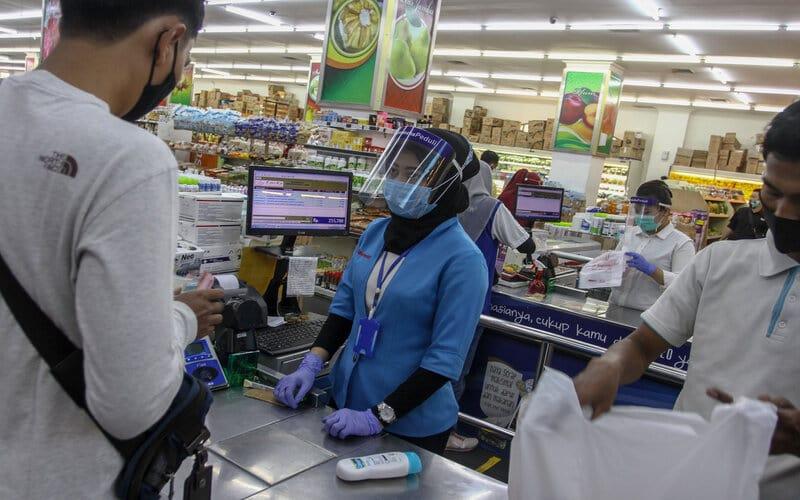 Petugas kasir mengenakan alat pelindung diri berupa masker, face shield dan sarung tangan ketika melayani pembeli di salah satu gerai penjualan kebutuhan pokok di Mal Pekanbaru, di Pekanbaru, Riau, Selasa (13/10/2020). Penggunaan masker, cuci tangan, pengukuran suhu tubuh dan penerapan jaga jarak, wajib diterapkan pengunjung maupun pekerja selama berada di pusat perbelanjaan tersebut guna mengantisipasi penyebaran Covid-19. - Antara/Rony Muharrman