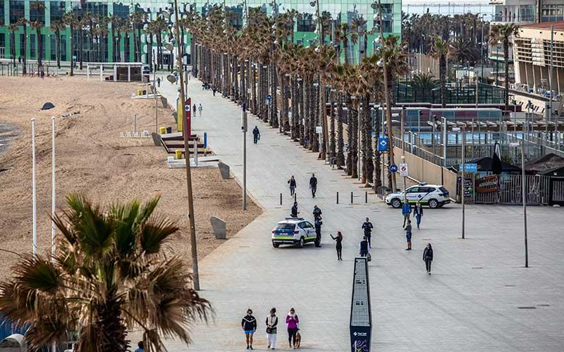 Polisi berpatroli di tepi pantai saat otoritas memberlakukan lock down di kawasan pantai Barceloneta di Barcelona, Spanyol, Minggu (15/3/2020). Bloomberg - Angel Garcia\n