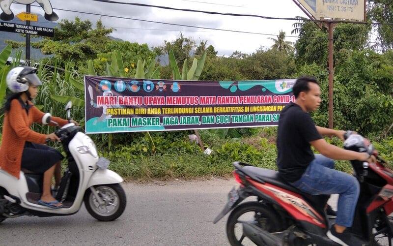 Sejumlah pengendara melintasi Jalan Palarik Aia Pacah Kota Padang Sumatra Barat tanpa menggunakan masker ketika sosialisasi protokol kesehatan terpajang di jalan itu. - Bisnis/Noli Hendra