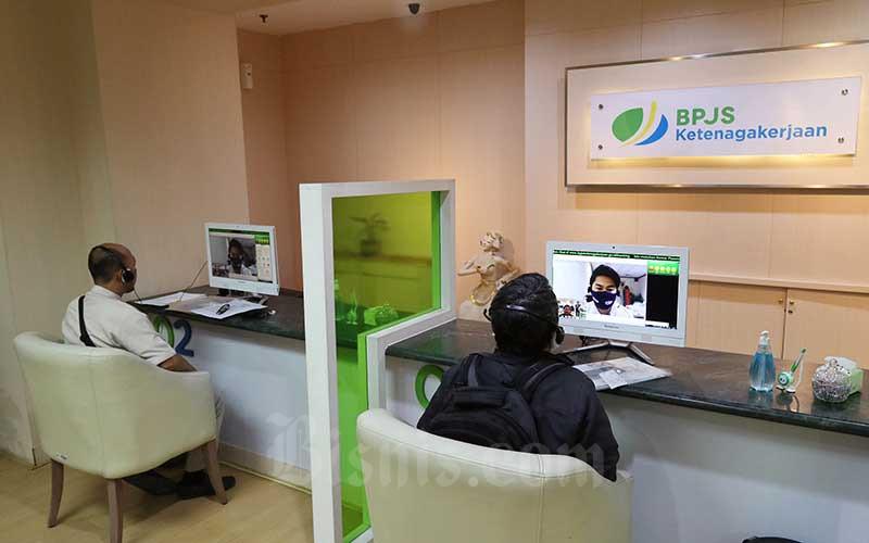 Peserta BP Jamsostek berkomunikasi dengan petugas pelayanan saat mengurus klaim melalui layar monitor dan tanpa kontak langsung di Kantor Cabang BP Jamsostek di Menara Jamsostek, Jakarta, Jumat (10/7/2020). - Bisnis/Eusebio Chrysnamurti