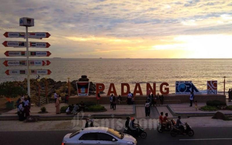 Warga menikmati matahari terbenam di Kota Pandang namun sejumlah orang belum patuh protokol kesehatan menggunakan masker. - Bisnis/Noli Hendra