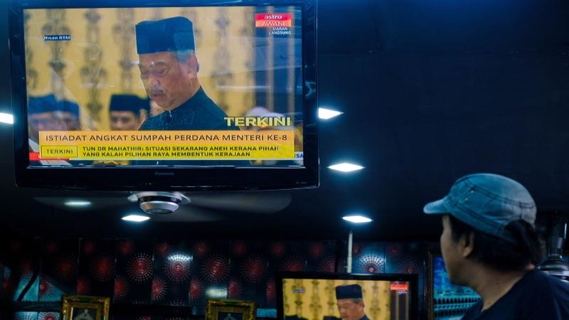 Siaran televisi menayangkan pengangkatan Muhyiddin Yassin sebagai Perdana Menteri kedelapan Malaysia oleh Raja Malaysia di Kuala Lumpur, Malaysia, Minggu (1/3/2020). - Bloomberg/Samsul Said