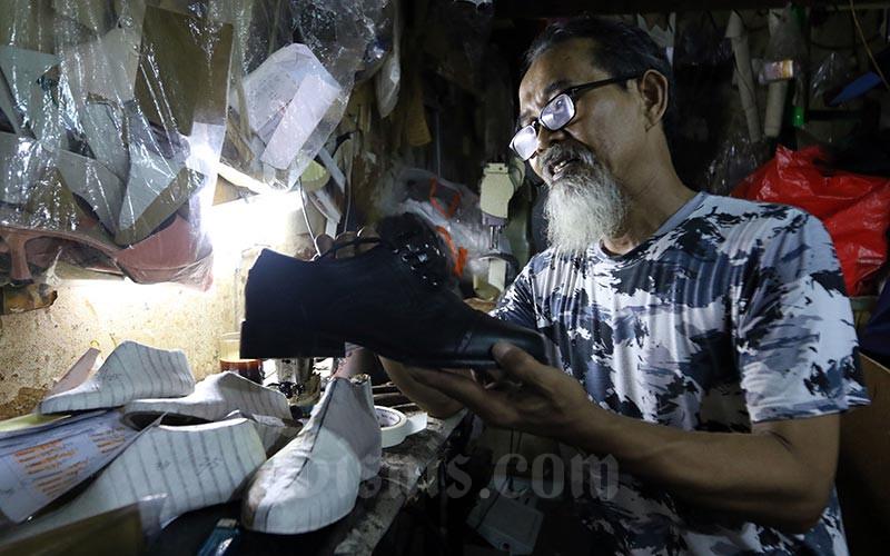 Ilustrasi pengrajin skala UKM menyelesaikan pembuatan alas sepatu./Bisnis - Abdullah Azzam