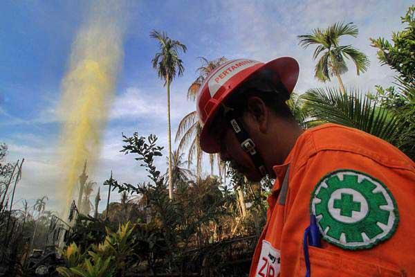 Petugas berjaga di lokasi ledakan sumur minyak ilegal yang telah padam di Desa Pasir Putih, Rantau Pereulak, Aceh Timur, Aceh, Kamis (26/4/2018). - ANTARA/Rahmad