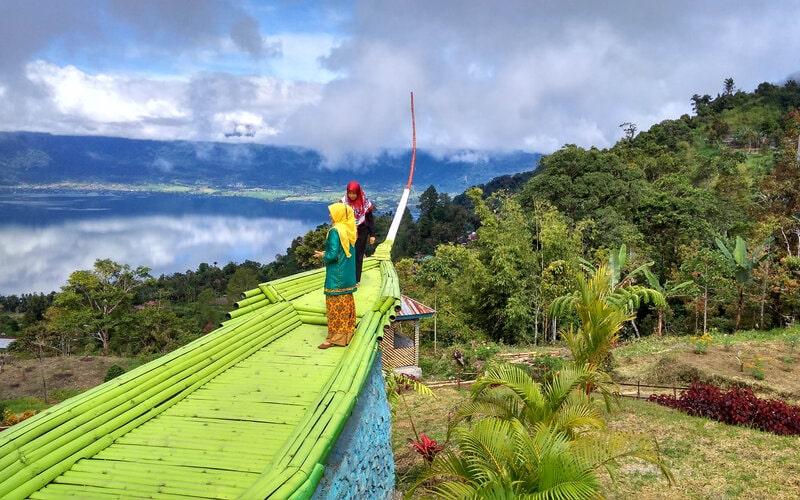 Para pengunjung tengah menikmati pemandangan di objek wisata Ambun Pagi Kabupaten Agam, Sumatra Barat yang memperlihatkan hamparan Danau Maninjau. Foto dokumen sebelum Covid-19. - Bisnis/Noli Hendra