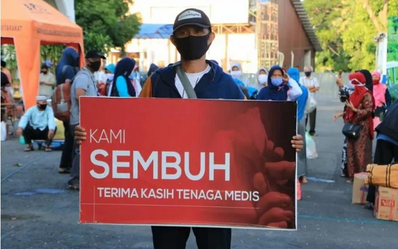 Seorang warga yang dinyatakan sembuh dari Covid-19 membawa spanduk bertuliskan ucapan terima kasih kepada tenaga medis saat dipulangkan dari tempat karantina di Asrama Haji Surabaya. - Antara