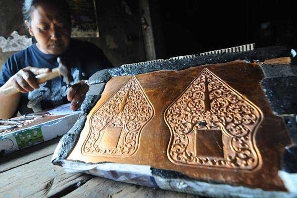 Perajin menatah tembaga saat pembuatan kerajinan tembaga motif gunungan wayang di Tumang, Cepogo, Boyolali, Jawa Tengah, Jumat (14/9/2018). - ANTARA/Aloysius Jarot Nugroho