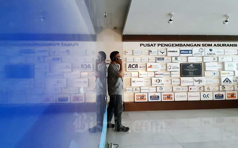 Karyawan beraktifitas di dekat deretan logo-logo perusahaan asuransi di Kantor Asosiasi Asuransi Umum Indonesia (AAUI) di Jakarta, Selasa (22/9/2020). Bisnis - Himawan L Nugraha