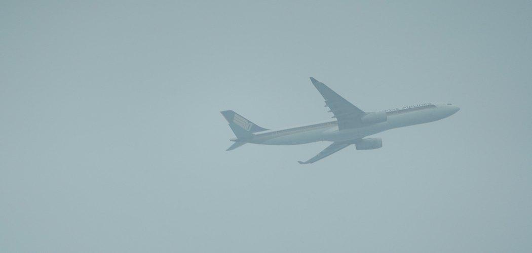 Sebuah jet penumpang yang dioperasikan oleh Singapore Airlines Ltd. terbang menembus kabut asap di Singapura. Dimas Adrian - Bloomberg