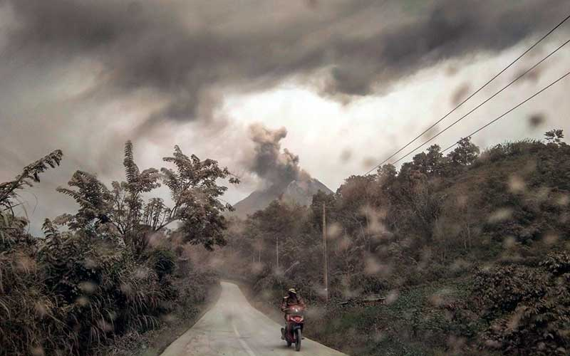 Pengendara melintas di jalan dengan latar belakang Gunung Sinabung yang menyemburkan material vulkanik di Desa Suka Tepu, Karo, Sumatera Utara, Jumat (14/8/2020). ANTARA FOTO - Tibta Peranginangin