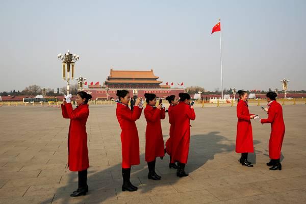 Para pekerja menggunakan ponsel mereka di Lapangan Tiananmen sebelum sidang pleno ketiga Konferensi Konsultatif Politik Rakyat Cina (CPPCC) di Beijing, China 10 Maret 2018. - Reuters