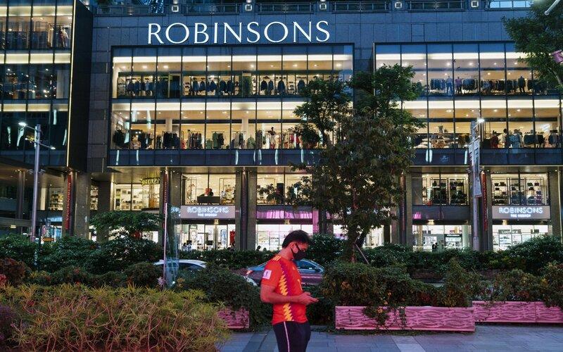 Seorang pria yang mengenakan masker berdiri di seberang pusat perbelanjaan Robinsons & Co. di Orchard Road di Singapura, pada hari Sabtu (25/6/2020) - Wei Leng Tay/Bloomberg.