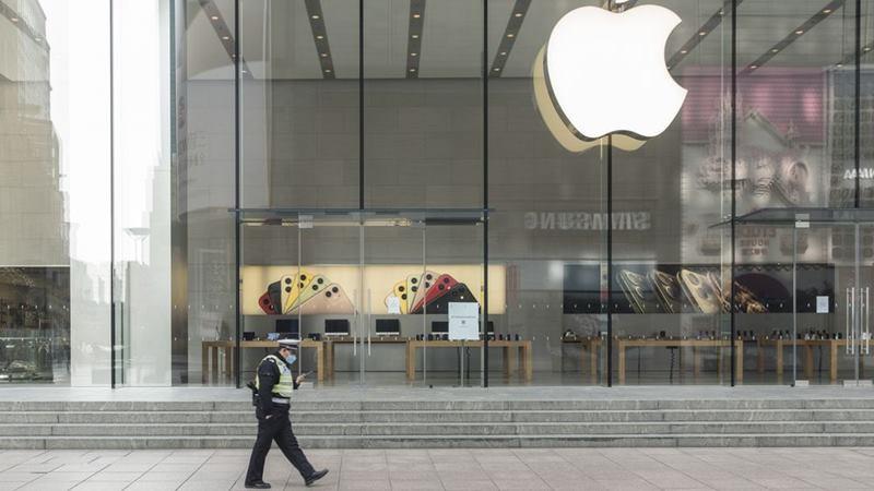 Seorang petugas polisi yang mengenakan masker pelindung berjalan melewati toko Apple yang tutup di Shanghai, China, pada 5 Februari 2020. -  Qilai Shen / Bloomberg
