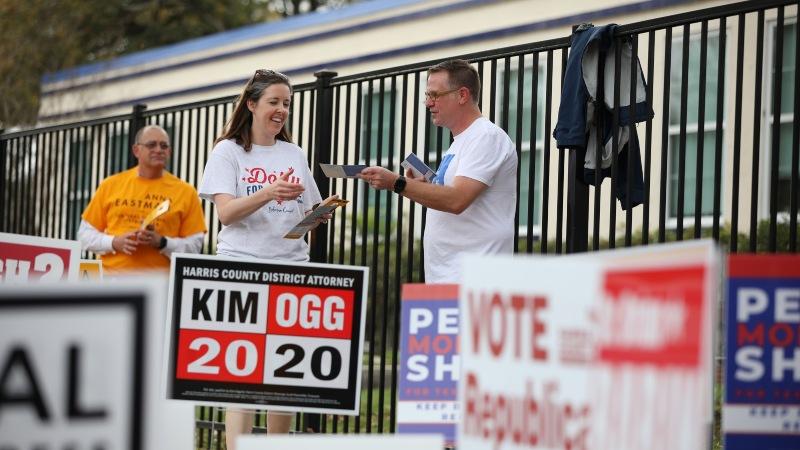 Relawan membagikan pamflet di luar Tempat Pemungutan Suara (TPS) dalam gelaran pemilihan pendahuluan di Houston, Texas, AS, Selasa (3/3/2020). - Bloomberg/Sharon Steinmann