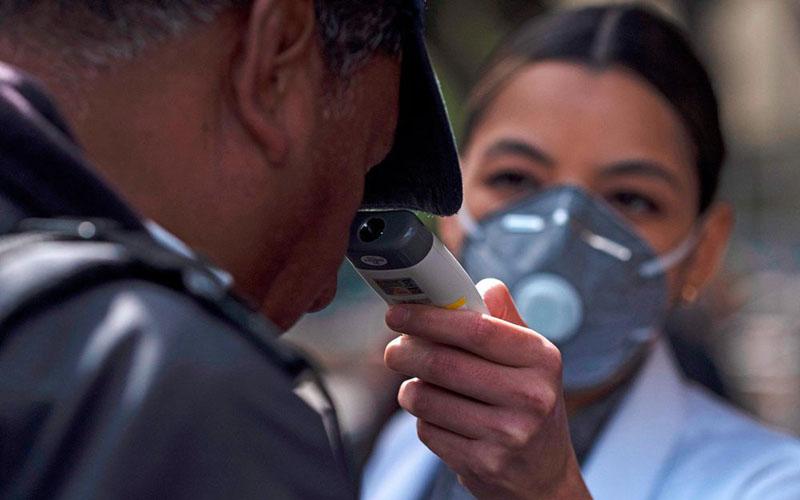Ilustrasi perawat memeriksa suhu seorang pria sebagai langkah awal untuk mendeteksi serangan virus corona Covid-19. - Bloomberg