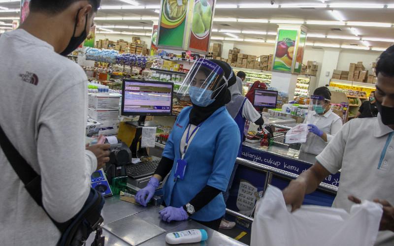 Petugas kasir mengenakan alat pelindung diri berupa masker, face shield, dan sarung tangan ketika melayani pembeli di salah satu gerai penjualan kebutuhan pokok di Mal Pekanbaru, Riau, Selasa (13/10/2020).  - ANTARA