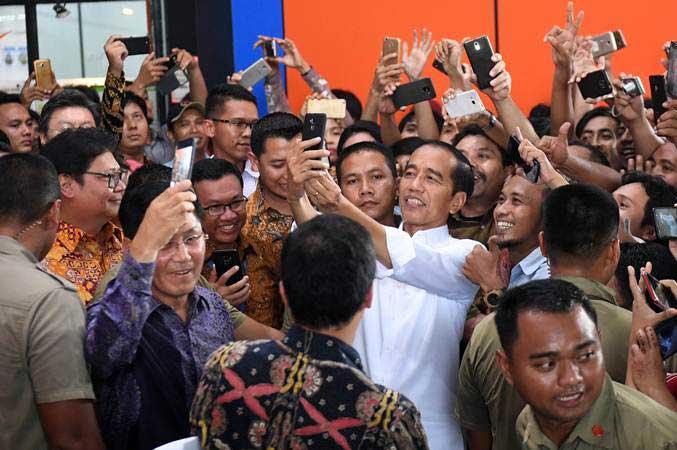 Presiden Joko Widodo berswafoto dengan para pekerja saat mengunjungi pabrik sepatu PT KMK Global Sports I, Tangerang, Banten, Selasa (30/4/2019)./Antara - Akbar Nugroho Gumay