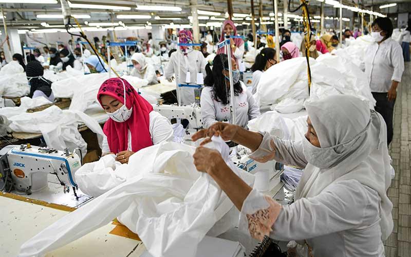 Pekerja perempuan memproduksi alat pelindung diri sebuah perusahaan garmen saat kunjungan Menteri Ketenagakerjaan Ida Fauziyah di Jakarta, Rabu (1/7/2020).  - ANTARA