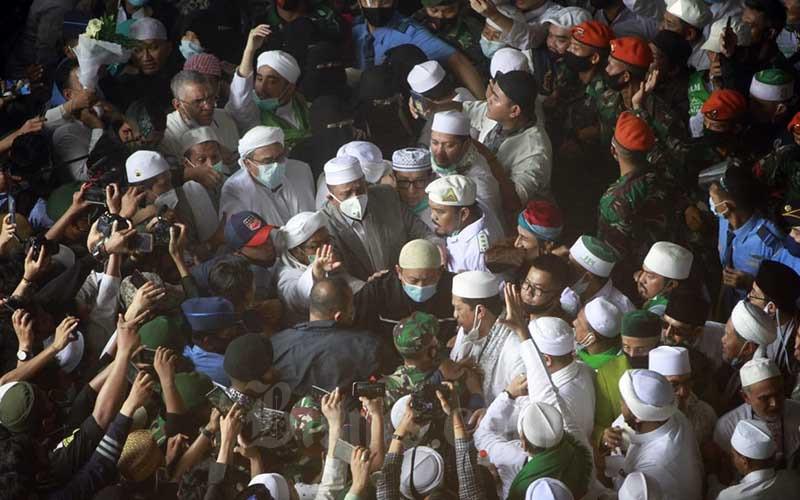 Habib Rizieq Shihab melambaikan tangan setelah tiba di Bandara Soekarno Hatta,  Tangerang, Selasa (10/11/2020). Kedatangannya disambut oleh ribuan simpatisan dari berbagai daerah di Indonesia. Bisnis - Himawan L Nugraha