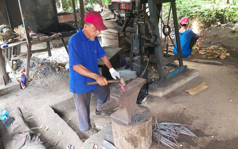Abbas, pelopor IKM Pandai Besi Rumbio Jaya Steel yang dirangkul PTPN V untuk pengadaan alat-alat panen perusahaan. IKM RJS mendapatkan kontrak pengadaan alat-alat panen senilai Rp1,6 miliar dan mendorong ekonomi warga setempat tetap bertahan pada masa pandemi. - PTPN V
