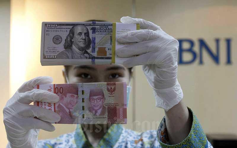 Karyawati menunjukan Uang Rupiah dan Dollar AS di salah satu kantor cabang Bank BNI di Jakarta, Kamis (3/9/2020).  Bisnis - Himawan L Nugraha