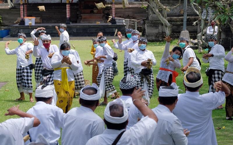 Sejumlah warga melempar ketupat ke arah warga lainnya dalam tadisi perang ketupat pada masa pandemi Covid-19 di Desa Kapal, Badung, Bali Kamis (1/10/2020). Tradisi tahunan yang biasanya melibatkan ratusan warga untuk wujud syukur atas hasil bumi. - Antara/Nyoman Hendra Wibowo