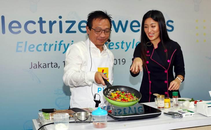 Kepala Divisi Niaga PLN Yudi Setyo Wicaksono (kiri) disaksikan Chef Priscil mencoba kompor induksi saat acara Elektrizen weeks di Jakarta, Senin (18/3/2019). - Bisnis/Abdullah Azzam