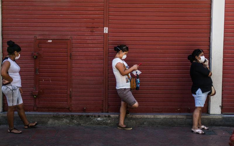 Warga Lima, ibu kota Peru, dengan mengenakan masker antre hingga keluar sebuah pasar swalayan karena menjaga jarak untuk menghindari penyebaran virus corona COVID-19. Foto diambil pada 23 Maret 2020. - Bloomberg