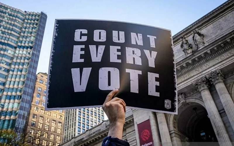 Seorang warga memegang poster imbauan setiap suara harus dihitung pada Pemilihan Presiden Amerika Serikat di depan Perpustakaan Umum New York, AS (4/11/2020). - Antara/Reuters