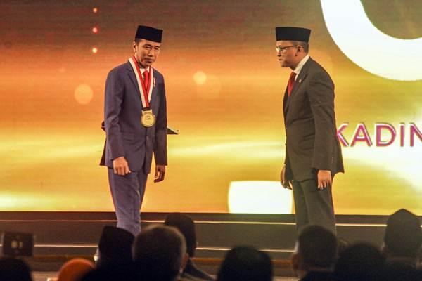 Presiden Joko Widodo (kiri) saat menerima penghargaan dari Ketua Umum Kadin Indonesia Rosan P. Roeslani (kanan) pada acara HUT ke-50 Kadin di Jakarta, Senin (24/9/2018). - Antara/Muhammad Adimaja