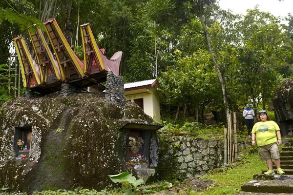 Wisatawan melintasi kuburan batu di Situs Megalitik Bori di Toraja Utara, Sulawesi Selatan, Minggu (23/4). - Antara/Adwit B Pramono