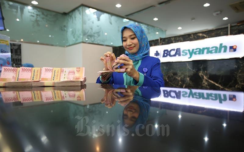 Karyawan menghitung uang rupiah di kantor cabang Bank BCA Syariah di Jakarta, Selasa (7/1/2020). Bisnis - Abdullah Azzam