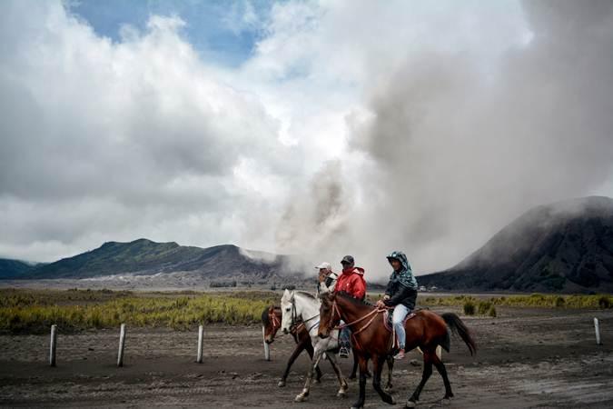 Tiga orang menunggang kuda dengan latar belakang Gunung Bromo yang menyemburkan abu vulkanis di Probolinggo, Jawa Timur, Jumat (15/3/2019). - ANTARA FOTO/Umarul Faruq