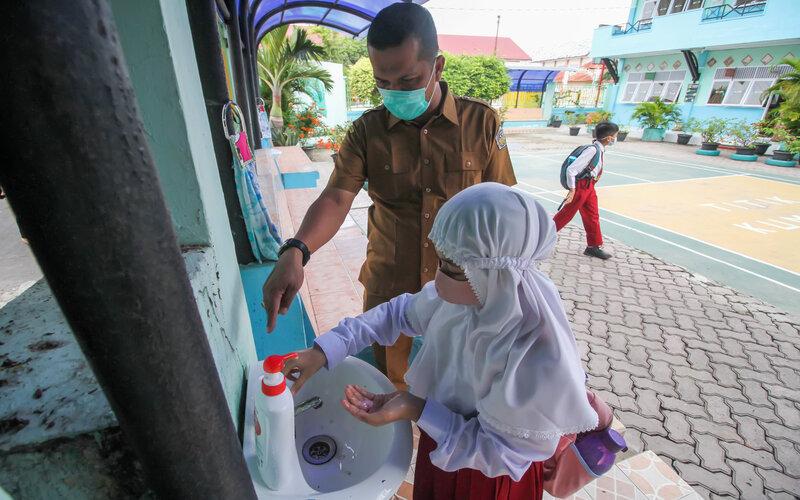 Siswa mencuci tangan sebelum memasuki ruang kelas. - Antara/Rahmad.