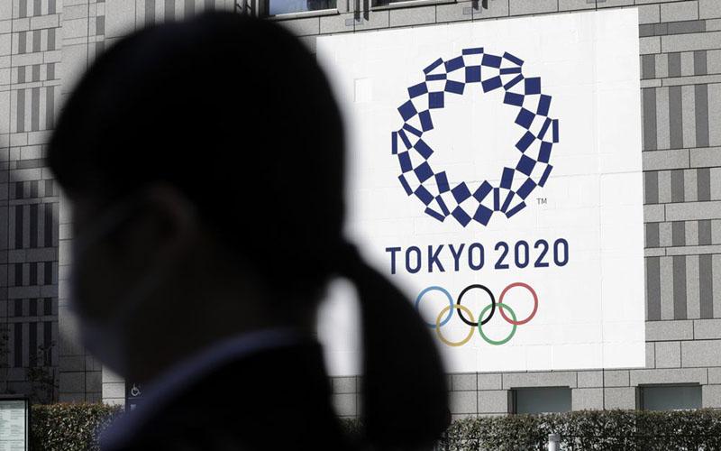 Seorang pejalan kaki melintas di Tokyo dengan berlatar belakang spanduk Olimpiade 2020./Bloomberg - Kiyoshi Ota