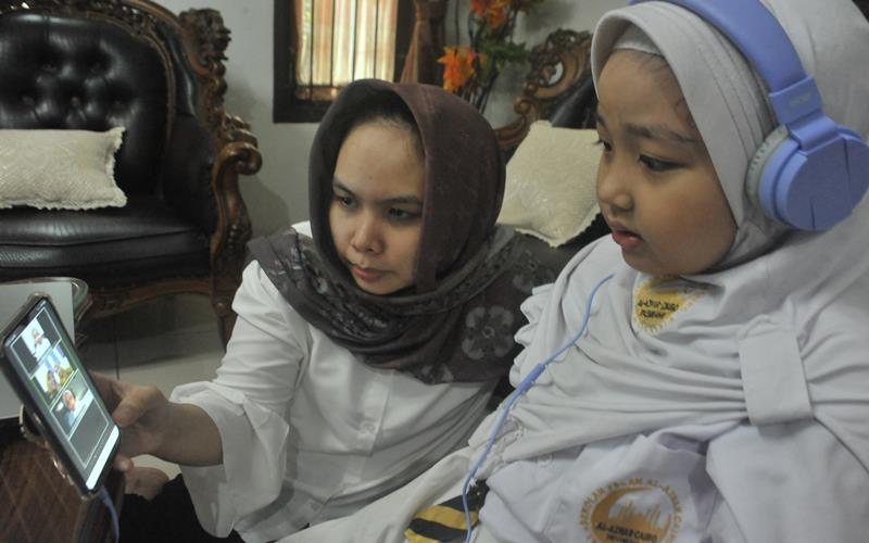 Siswa Sekolah Dasar didampingi orang tua melakukan Pembelajaran Jarak Jauh (PJJ) dengan sistem daring pada hari pertama tahun ajaran baru 2020-2021 di Palembang, Sumatera Selatan, Senin (13/7/2020). ANTARA FOTO - Feny Selly
