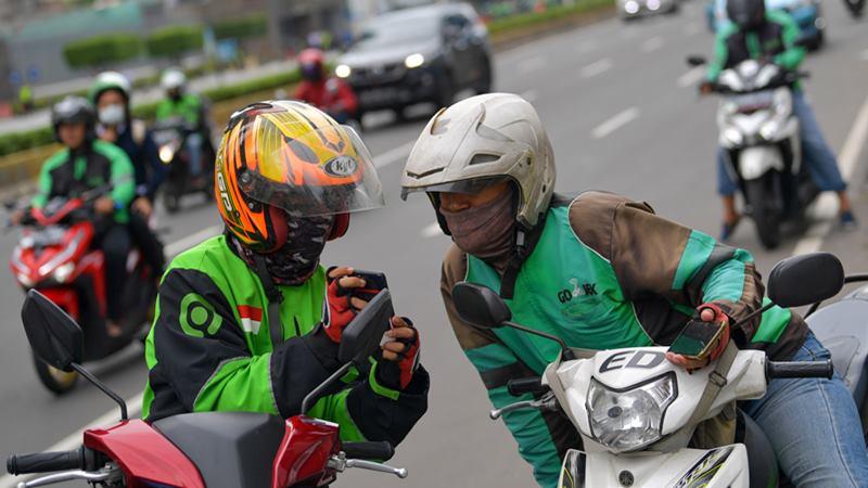 Dua orang pengemudi ojek online berbincang di Jalan Thamrin, Jakarta, Senin (17/2/2020). - ANTARA / M Risyal Hidayat\n