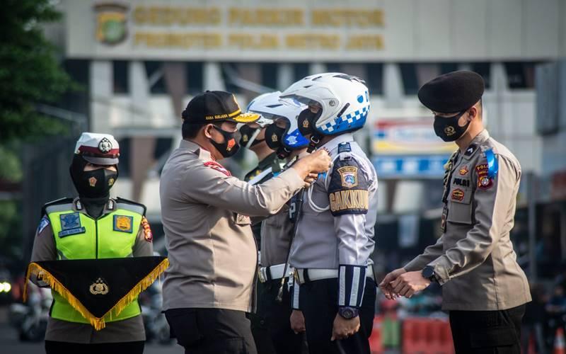 Kapolda Metro Jaya Irjen Pol Nana Sudjana (kedua kiri) menyematkan pita tanda operasi kepada perwakilan petugas dalam Apel gelar Pasukan Operasi Patuh Jaya Tahun 2020 di Polda Metro Jaya, Jakarta, Kamis (23/7/2020). - Antara