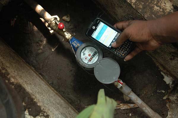 Seorang karyawan PT Aetra Air Jakarta mengecek meteran melalui fitur Global Positioning System (GPS) di sebuah perumahan di sekitar Rawamangun, Jakarta, Selasa (14/6).  - Bisnis.com